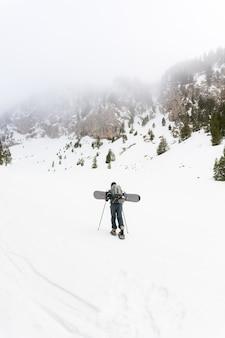 Free rider avec raquettes et snowboard sur le dos.
