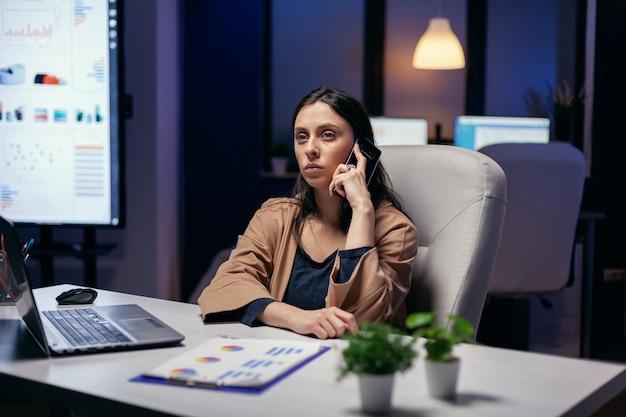 Freelance bourreau de travail concentré discutant au téléphone le soir. femme entrepreneur travaillant tard le soir dans une entreprise faisant des heures supplémentaires au cours d'un appel téléphonique.