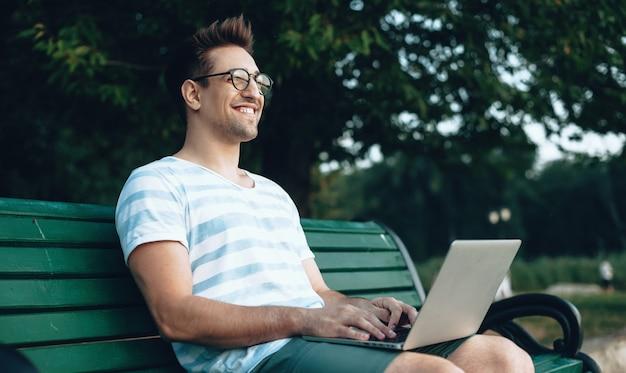 Freelance caucasien avec des lunettes travaillant à l'ordinateur sur un banc dans le parc