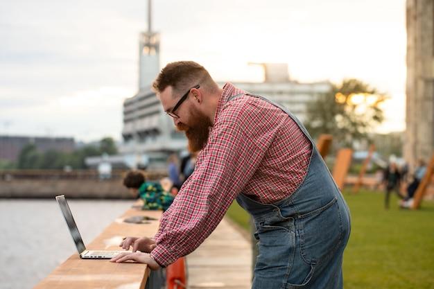 Freelance homme barbu portant une salopette bleue travaillant sur un ordinateur portable au remblai à l'extérieur. travail à distance, travail à distance.