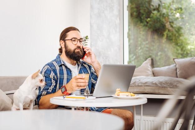 Freelance prospère occupé se sentant détendu tout en buvant du café au lait travaillant sur un ordinateur portable
