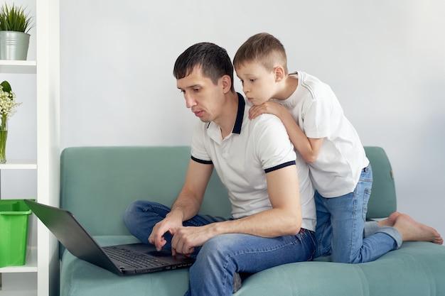Freelance travaillant à domicile dans des conditions confortables. homme essayant de travailler, l'enfant empêche son père de travailler.