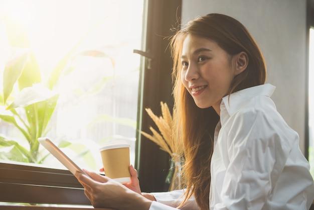 Freelancer femme casual asiatique à l'aide de tablette et plan d'écriture et sourire avec une tasse de café au café-restaurant