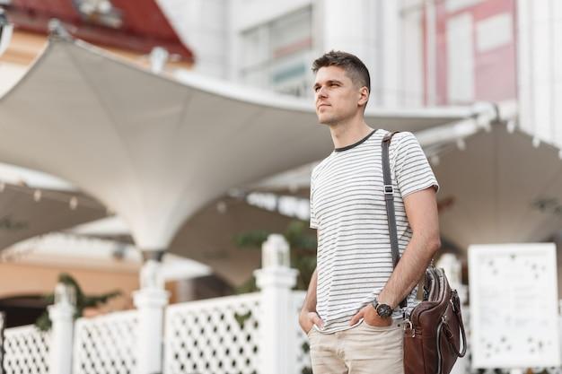 Freelancer moderne jeune homme élégant dans un sac à la mode en cuir dans un t-shirt à rayures à la mode avec une coiffure se dresse sur une rue