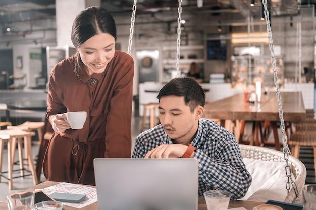 Freelances réussies. couple de pigistes intelligents à succès profitant du temps de travail à la cafétéria
