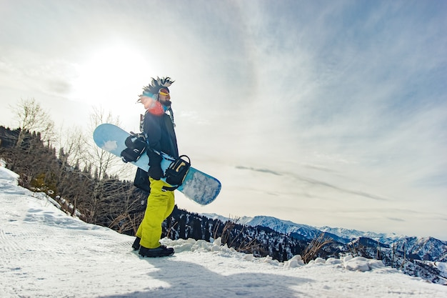 Le freerider de snowboard dans le chapeau drôle dans les montagnes se prépare à descendre
