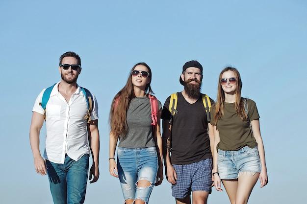 Freinds en jeans et shorts avec des sacs à dos marchant en plein air