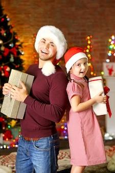 Frère aîné et petite soeur en bonnet de noel avec cadeau pendant la saison de noël