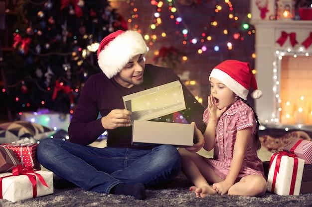 Frère aîné et petite sœur en cadeau d'ouverture de chapeau de père noël pendant la saison de noël