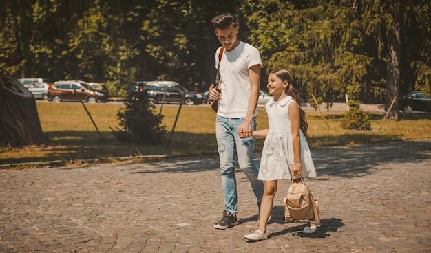 Frère aîné et sœur cadette marchant sur la rue de la ville