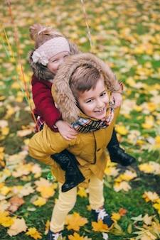 Frère chevauche sa petite sœur sur le dos dans le parc à l'automne