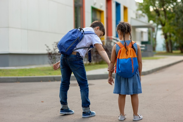 Un frère d'écolier avec un sac à dos bleu prend sa petite sœur par la main pour entrer dans le