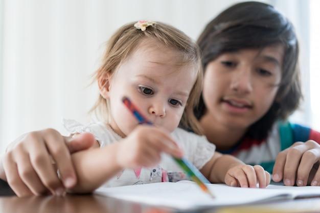 Frère jouant et dessinant avec sa petite soeur
