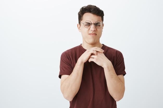 Frère mécontent de laver la vaisselle sale. portrait de mec malheureux dégoûté fronçant les sourcils à lunettes rondes