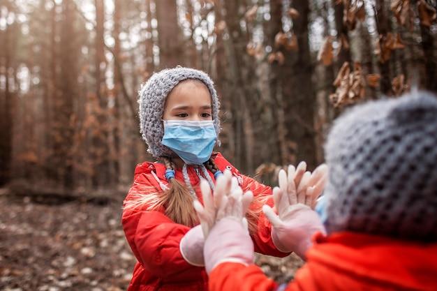 Frère mignon en manteaux rouges portant des masques respiratoires et des gants médicaux jouant le gâteau de galette