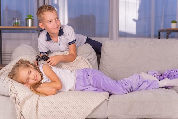 Frère réveille sa sœur avec un réveil qui appelle fort et ne veut pas se lever pour l'école