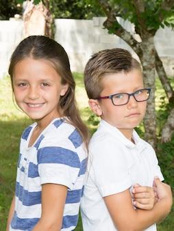 Frère et sœur assis dehors. garçon triste avec des lunettes
