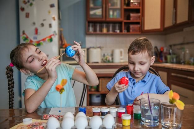 Frère et soeur brune décorent les œufs de pâques assis à la table à la maison dans la cuisine