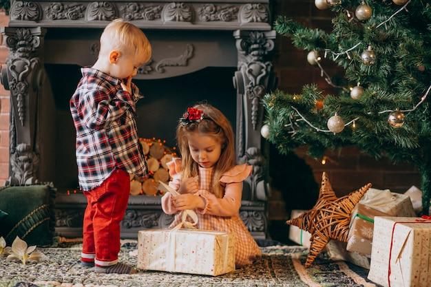 Frère avec soeur emballant des cadeaux de noël par sapin de noël