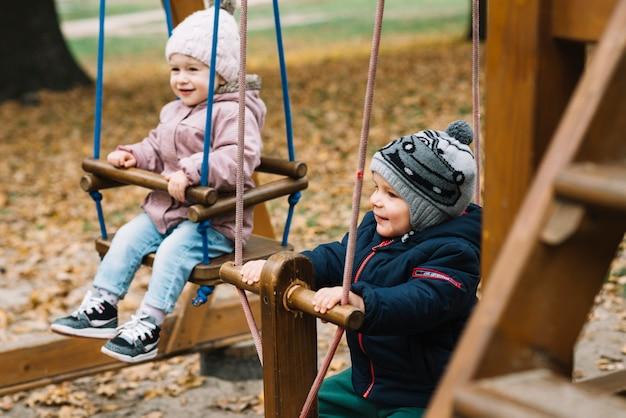 Frère et soeur enfant en bas âge sur la cour de récréation d'automne
