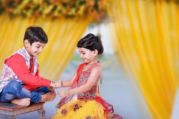 Frère et soeur indiens mignons célébrant le festival de raksha bandhan,