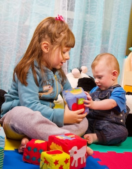 Frère et soeur jouant avec un cube de couleur douce