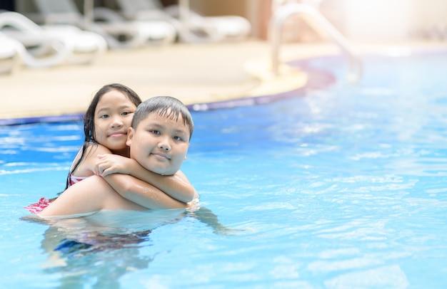 Frère et soeur jouent de l'eau dans la piscine