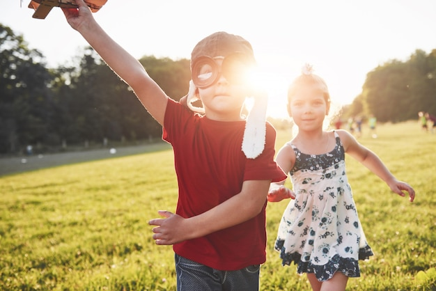 Frère et sœur jouent ensemble. deux enfants jouant avec un avion en bois en plein air