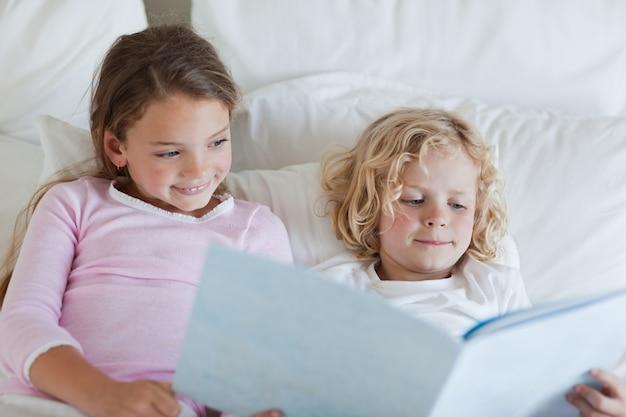 Frère et soeur lisant l'histoire de l'heure du coucher