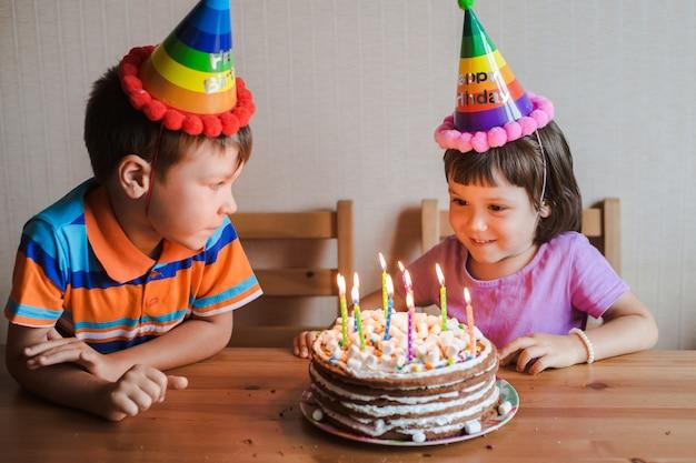 Frère et sœur mangeant un gâteau d'anniversaire avec des bougies qui soufflent et s'étreignent.