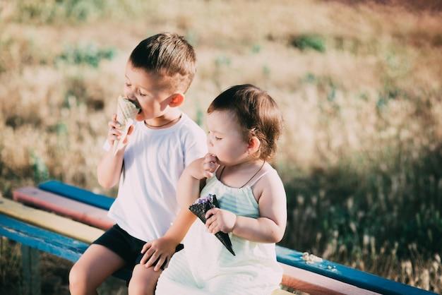 Frère et soeur mangeant de la glace sur le banc dans le terrain de jeu est très mignon