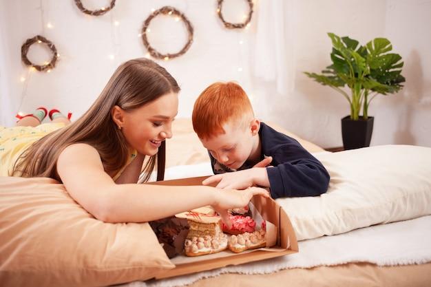 Frère et soeur mangent des gâteaux au lit, s'amusent