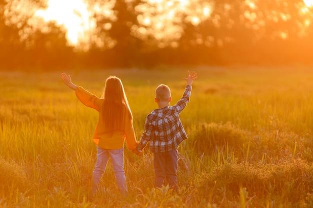 Frère et sœur sur une promenade dans la nature au coucher du soleil.
