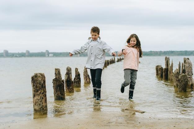 Frère et soeur s'amusent et jouent près de la mer