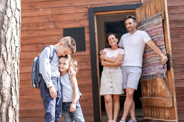 Frère et sœur s'embrassent, ils attendent le bus scolaire sur le pas de la porte de leur maison, les parents les regardent, admirent leurs sympathiques enfants.