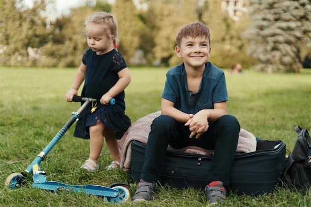 Frère et sœur avec un scooter dans le parc