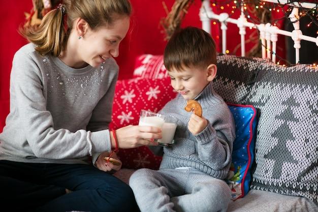Frère et sœur, se serrant dans leurs bras, s'amusant, dans la maison décorée pour la nouvelle année. vacances de noël