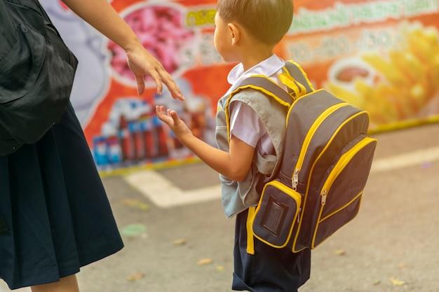 Frère et soeur se serrent la main de l'école.