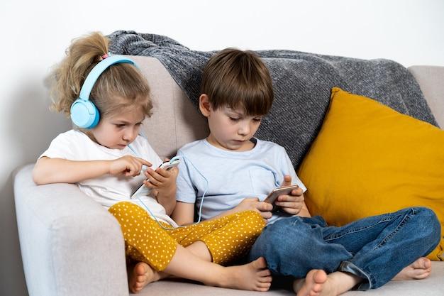 Frère et sœur sont assis à la maison sur le canapé avec une fille de smartphones dans un concept d'écouteurs pour enfants et