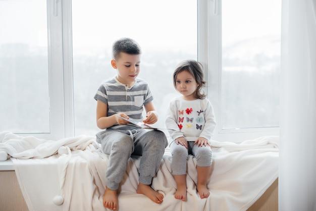 Frère et sœur sont assis sur le rebord de la fenêtre et lisent un livre. bonheur, famille