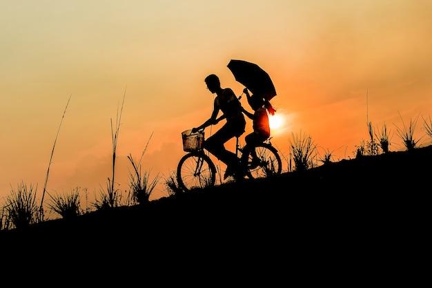 Frère avec soeur à vélo au coucher du soleil