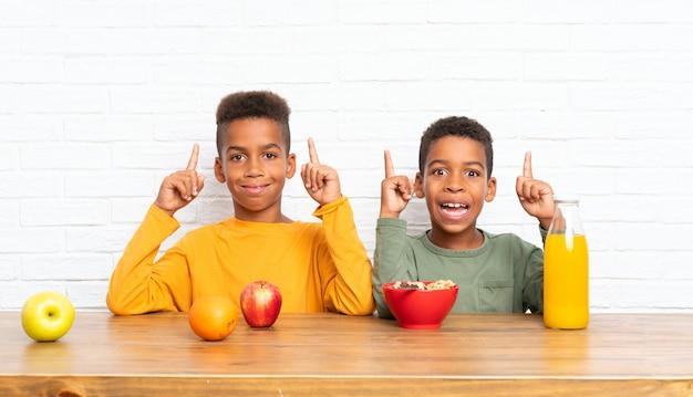 Frères afro-américains prenant son petit déjeuner et pointant vers le haut