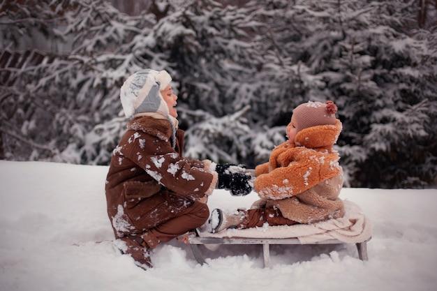 Les frères amusants d'hiver jouent dans la neige et font un bonhomme de neige