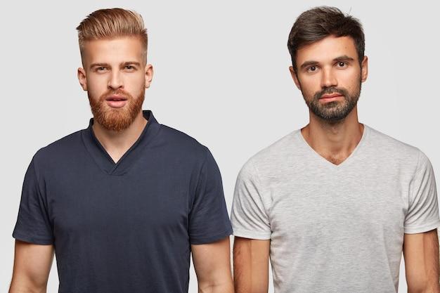 Frères barbus posant contre le mur blanc