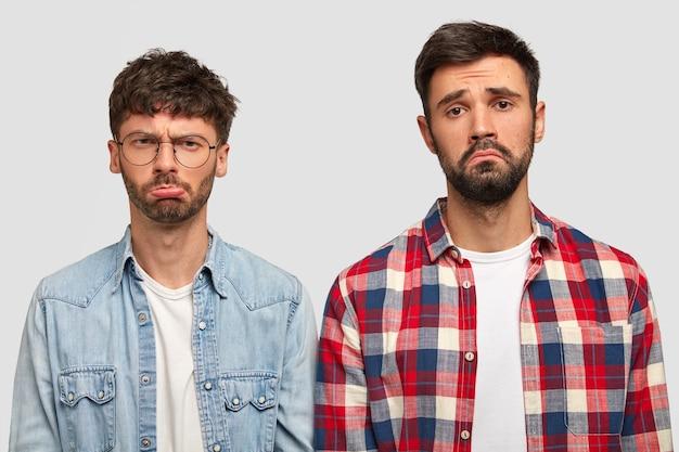 Les frères bouleversés ont des expressions malheureuses, des visages froncés de mécontentement, étant de mauvaise humeur après avoir regardé un match de football, réalisent le jeu lâche de leur équipe préférée, isolé sur un mur blanc