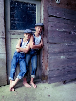 Frères avec bretelles et chapeaux s'appuyant sur un vieux bâtiment en bois sous la lumière du soleil