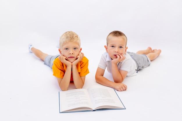 Frères couchés sur un fond blanc isolé et lisant un livre