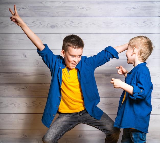 Frères heureux et amicaux pendant le match. un garçon aîné montre une pose amusante et un autre plus petit se moque de lui avec joie. deux amis émotifs et positifs.