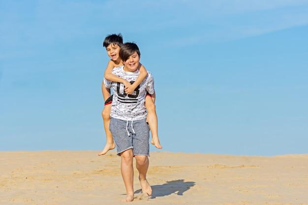 Frères jouant dans les dunes