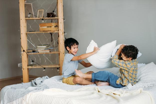 Frères jouant avec des oreillers sur le lit des parents à la maison